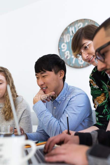 Fröhliche multirassische Kollegen Zusammensitzen mit Gadgets am Tisch — Stockfoto