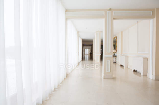 Perspective view to big light hallway in hotel. — Stock Photo