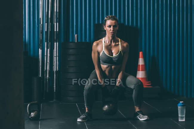 Forme femme accroupie avec kettlebell au cours de la séance d'entraînement de fesses dans une salle de sport — Photo de stock