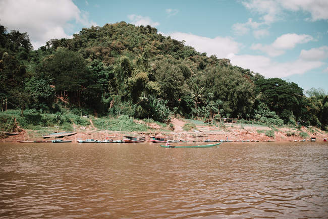 Small boats sailing in dirty water at hill covered with jungle forest. — Stock Photo