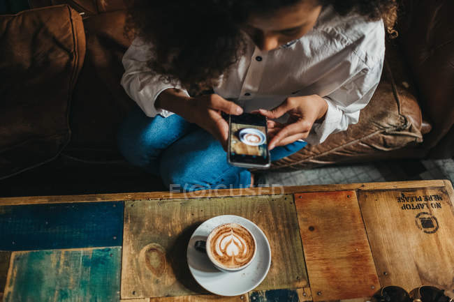 Par dessus de la femme assise dans café et prise de tasse de latte avec smartphone — Photo de stock
