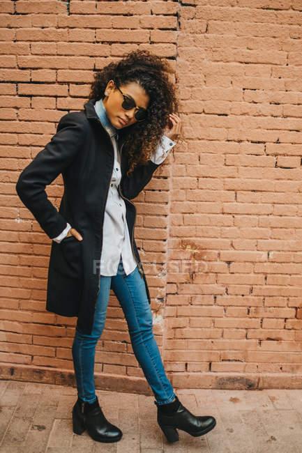 Elegante mujer rizada posando en la pared de ladrillo - foto de stock