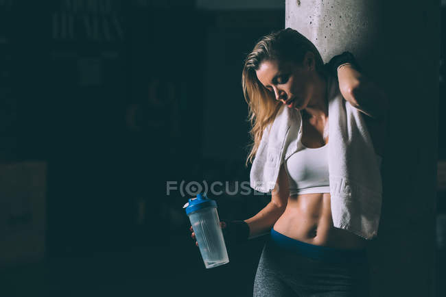 Fit blonde tired woman resting after working out — Stock Photo