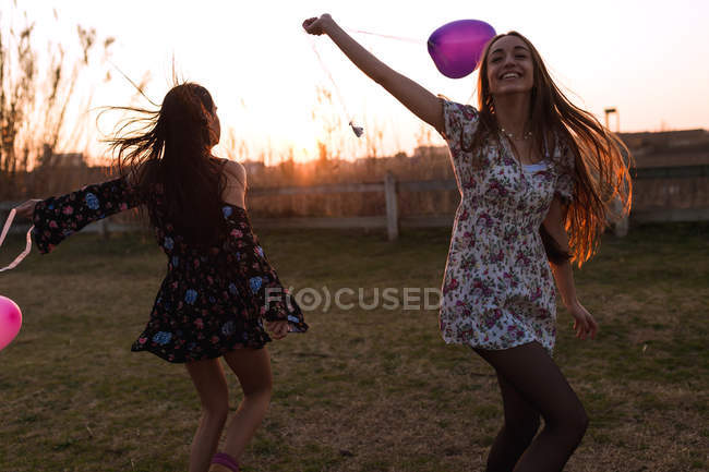 Two cheerful girls running with heart-shaped balloons having fun at nature. — Stock Photo