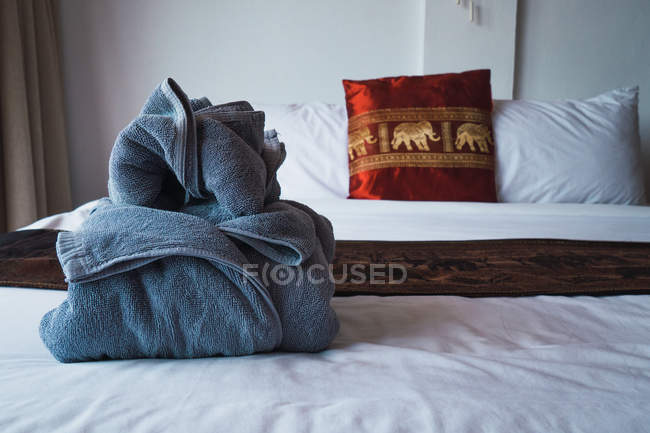 Gray colored towel placed on bed in hotel. — Stockfoto