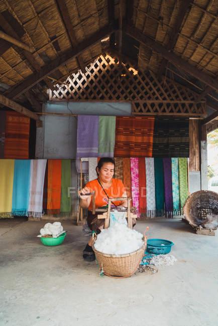 LAOS- FEBRERO 18, 2018: Mujer sonriente trabajando con tela en el patio - foto de stock