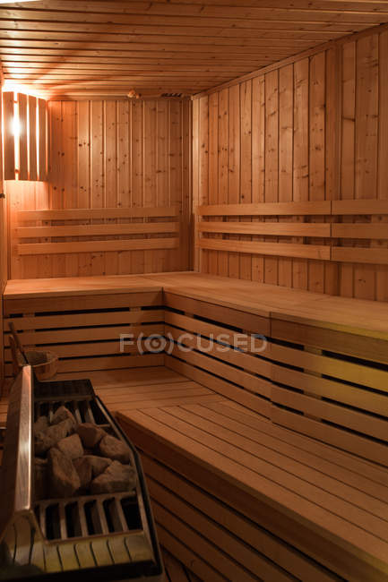 Interior of small wooden sauna room with seats and furnace. — Stock Photo