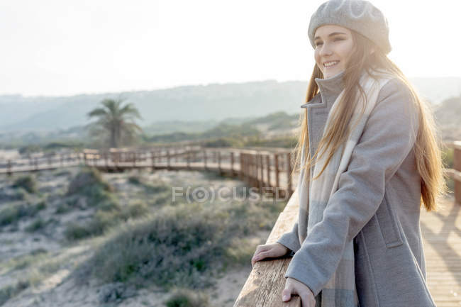 Cheerful woman standing at boardwalk and leaning on handrail — Stock Photo