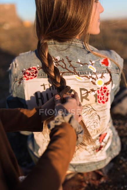 Обтинання жіночий руки переплетений волосся з подругою в Сонячний природи — стокове фото