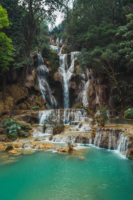 Beautiful waterfalls flowing to tropical lake with turquoise water — Stock Photo