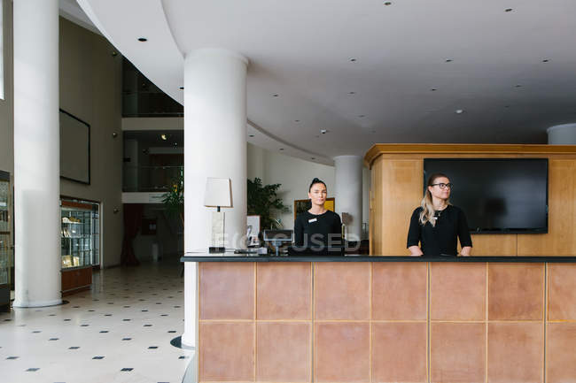 Pretty staff women standing at counter on reception in hotel — Stock Photo