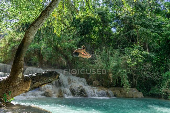 Man in midair jumping to turquoise lake water — Stock Photo