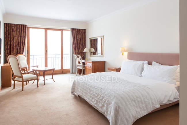 Intérieur de la chambre d'hôtel avec lit blanc et lampe allumée — Photo de stock
