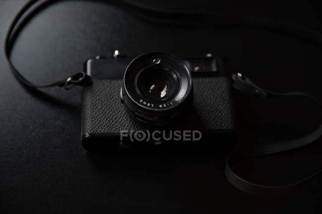 Vintage camera lying on black background — Stock Photo