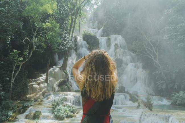 Vue arrière de la femme regardant une cascade tropicale — Photo de stock