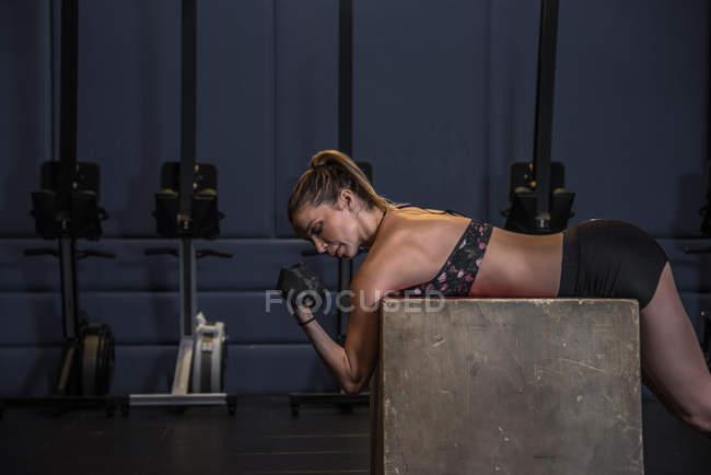 Femme blonde fit, soulevant des poids pendant que vous travailler dans une salle de sport — Photo de stock
