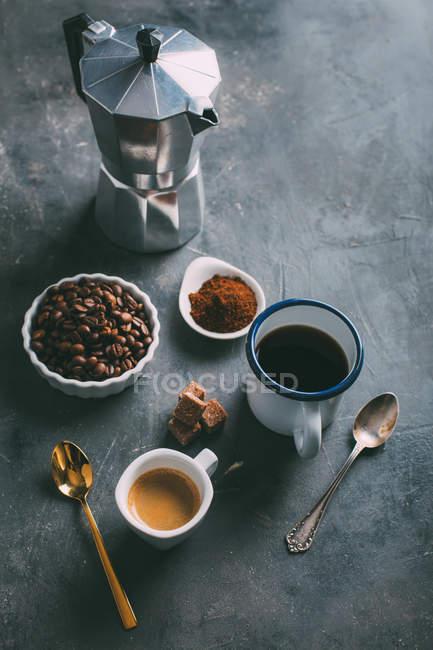 Чашки кави та інгредієнти з кавоваркою на стіл — стокове фото