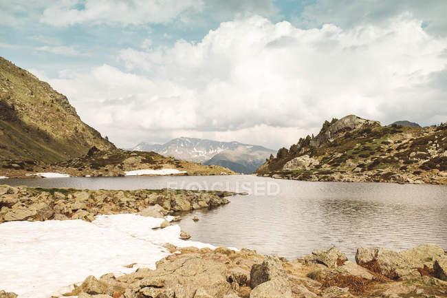 Paesaggio di piccole colline e lago in giornata nuvolosa . — Foto stock