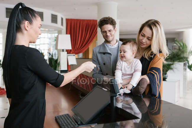 Staff worker giving key to young family at hotel reception — Stock Photo