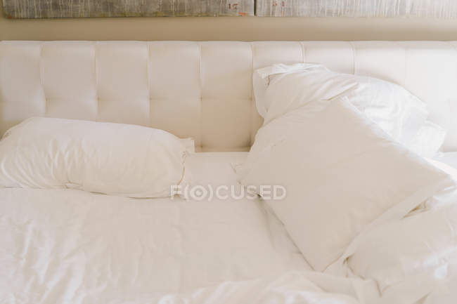 Messy undone bed with white sheets in daylight. — Fotografia de Stock