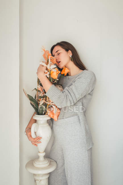 Sensual young woman embracing orange flowers in vase with closed eyes — Stock Photo