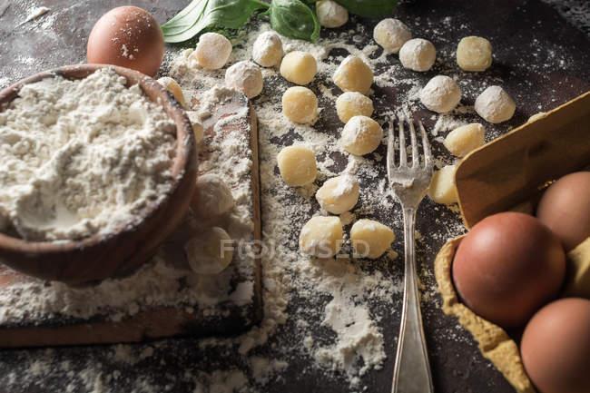 Direkt oberhalb Blick auf rohe Gnocchi und Zutaten auf Küchentisch — Stockfoto