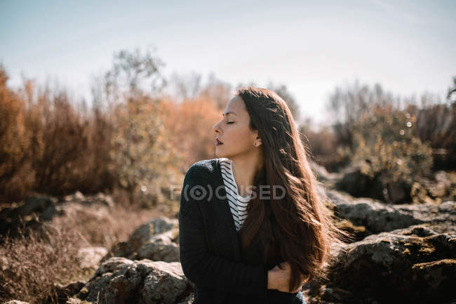 Sensual brunette woman sitting in nature and enjoying sun with eyes closed — Stock Photo