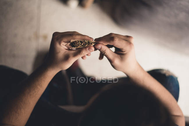 From above unrecognizable person sitting and rolling joint with weed. — Stock Photo