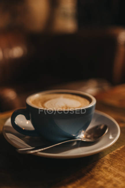 Blue ceramic cup of milky latte with heart drawn on foam. — Stock Photo