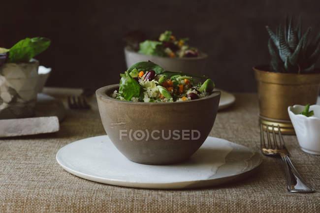La naturaleza muerta de la ensalada de la quinua y los frijoles rojos en la escudilla a la mesa - foto de stock