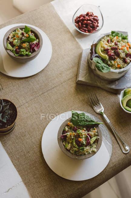 Platos de ensaladas con quinoa y poroto en mesa - foto de stock