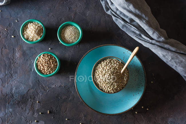Directly above view of ceramic bowls filled with cereals and wheat flakes on table — Stock Photo