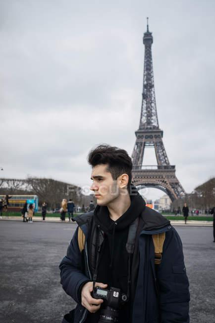 Uomo giovane turista con la macchina a piedi dalla Torre Eiffel — Foto stock