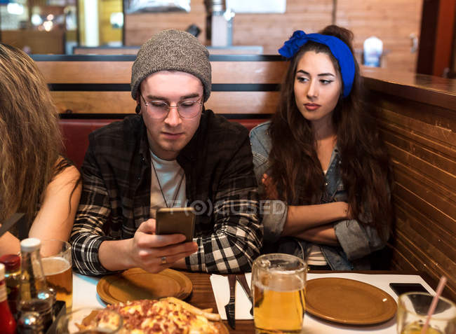 Young friends spending time at cafeat table in restaurant. — Stock Photo