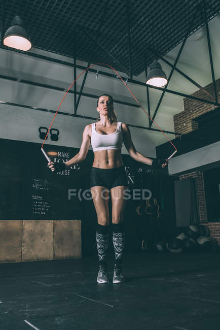 Fit blonde woman jumping with rope during working out in gym — Stock Photo