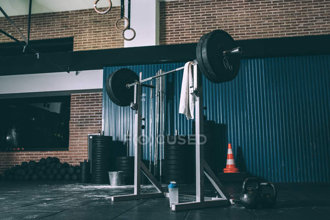 Stand with bar weight in empty gym — Stock Photo