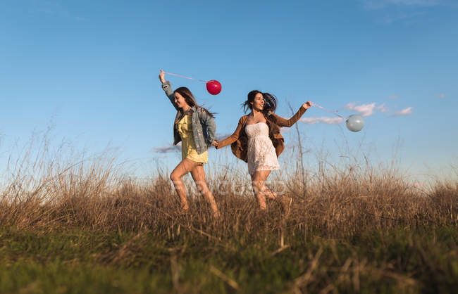 Young women holding hands and cheerfully running with balloons in nature. — Stock Photo