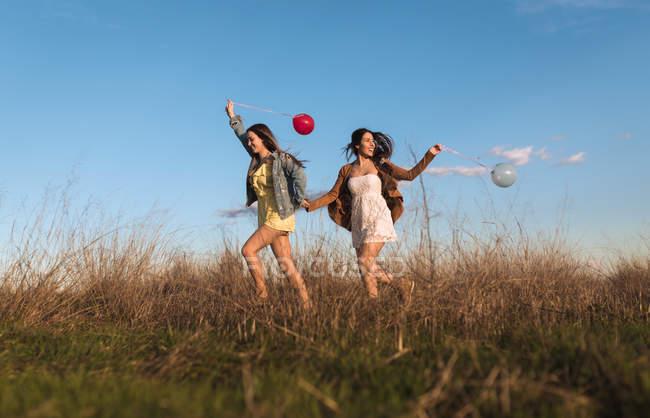 Junge Frauen Hand in Hand und laufen fröhlich mit Ballons in der Natur — Stockfoto