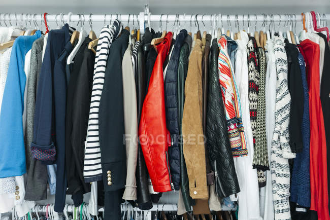 Wardrobe with different stylish clothes on hangers — Stock Photo