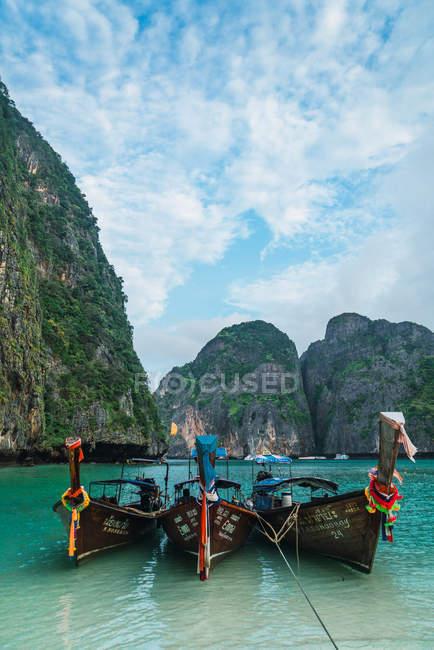 Three boats moored at shore of tropical lagoon — Stock Photo