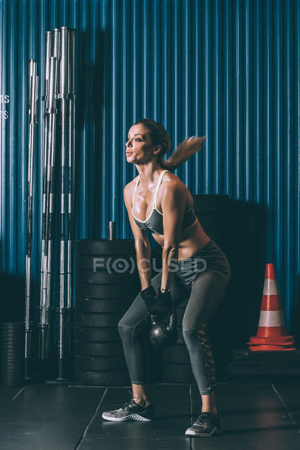 Entraînement de fesses femme blonde fit avec kettlebell en gym — Photo de stock