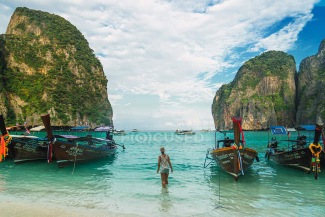 Rear view of girl walking in ocean among moored boats — Stock Photo