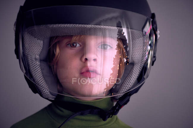 Очаровательный мальчик в мотоциклетном шлеме и смотрит в камеру . — стоковое фото