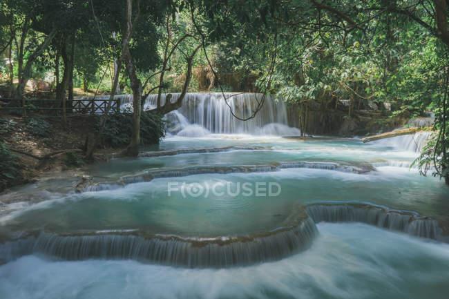 Idílica cascada con aguas color turquesa en el bosque tropical - foto de stock
