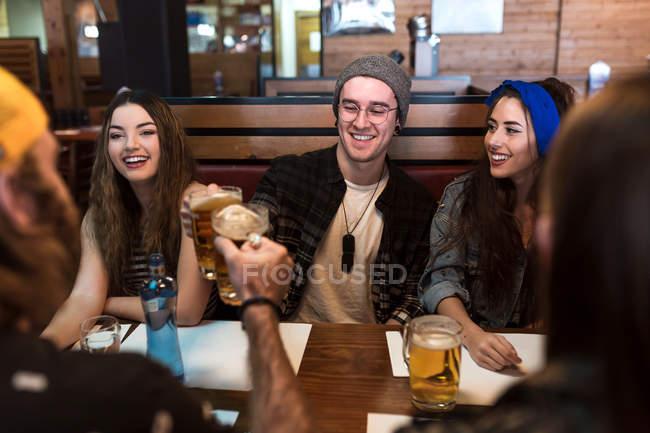 Amigos felizes, tilintar de copos de cerveja na mesa no restaurante — Fotografia de Stock