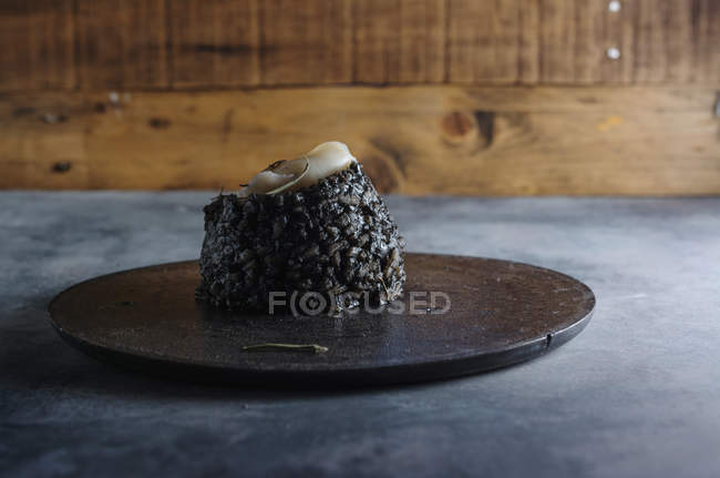 Side view of black rice with cuttlefish on black dish — Stock Photo