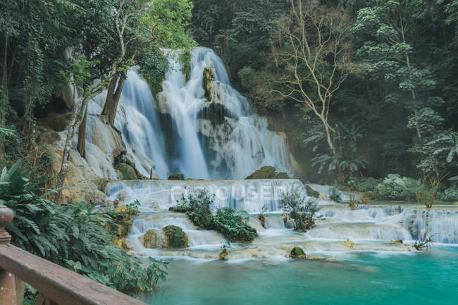Distant view of waterfall with turquoise water at tropical forest — Stock Photo