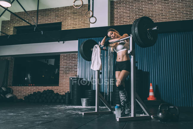 Fit blonde woman resting after lifting bar weights in gym ll — Stock Photo