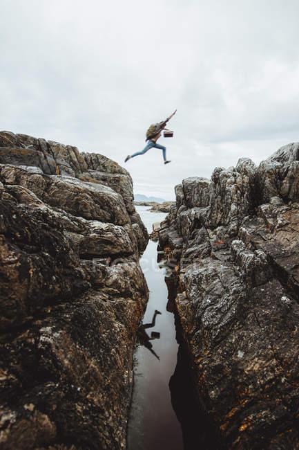 Seitenansicht eines nicht wiedererkennbaren Wanderers mit Rucksack, der zwischen Felsen über den Fluss springt. — Stockfoto