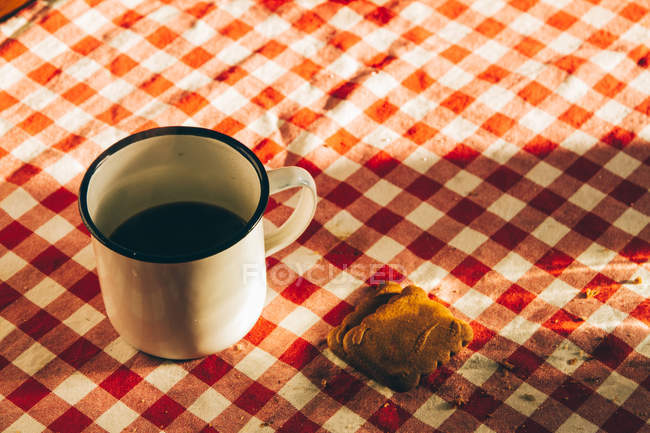 White metal cup with coffee on checkered tablecloth with cookies. — Stockfoto